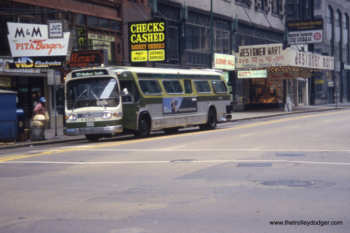 "CTA bus 9409 at Washington and Dearborn on August 4, 1985, heading west on Route 20 - Madison. Chicagoans ""of a certain age"" may recall Stop & Shop, which was sort of like a mini-Treasure Island type grocer in the space occupied by the Designer Mart in this photo. The entire block (Block 37) where these stores were located was declared ""blighted"" by the City and nearly all buildings were leveled in 1989. Block 37 remained undeveloped for more than a decade, and temporarily housed a skating rink in winter."