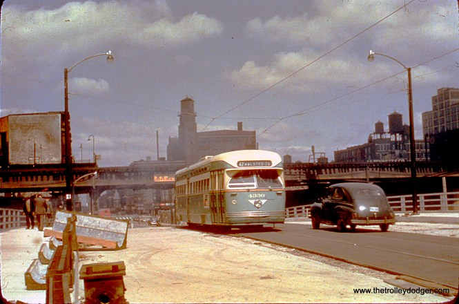 "CTA 4330, a Pullman PCC, heads south on Halsted, crossing a brand-new bridge over the Congress Expressway, then under construction, in 1950. In the background is the Met ""L"" main line, which remained in use at this location until June 1958. The PCC is signed for Route 42, Halsted-Downtown. M. E. adds, ""The streetcar's destination sign reads route 42, but route 42 did not run when and where the picture was taken (Halsted at Congress). At that spot, only route 8 ran. The correct sign would have said 8 Halsted-79."" Jim Huffman adds, ""The motorman saw the 79th thru the little view window & stopped there."""
