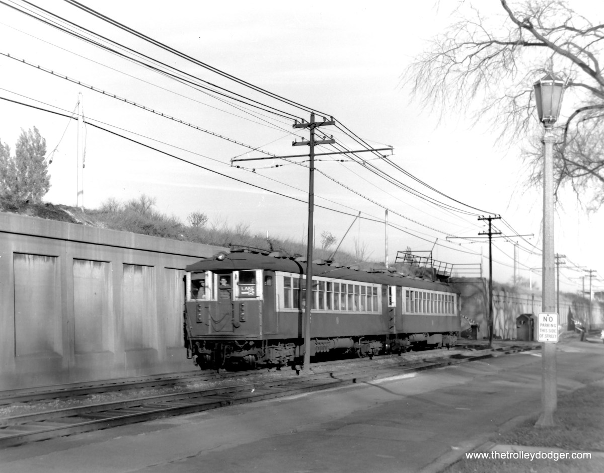 "October 27, 1962 was the last day of ground-level operation on the CTA Lake Street ""L"". The following day, service was relocated to the adjacent Chicago & North Western embankment. Here, we see a pair of 4000s heading west on South Boulevard at Kenilworth."