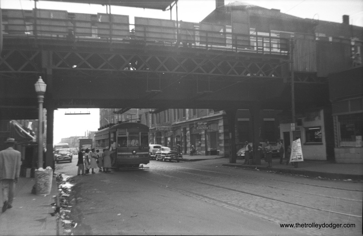 """CTA 6180, a one-man car, picks up passengers at an """"L"""" station in the early 1950s."""
