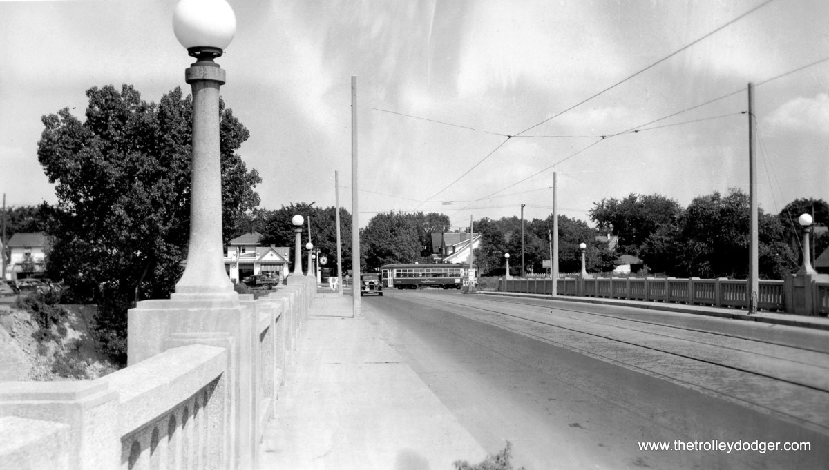 "Indiana Service Corp View across the Broadway bridge, showing double truck car in distance, August 18, 1940. (But what city is this?) Mike Peters writes: ""he ISC city car is in Fort Wayne, a block away from the south end of the Broadway line. The bridge carries Bluffton Road and the ISC interurban to Bluffton over the Saint Marys River. A good map of the Ft. Wayne system can be found in ""Fort Wayne's Trolleys"" (George Bradley). ISC did provide service in several smaller cities, but these lines did not survive the 1930's."""