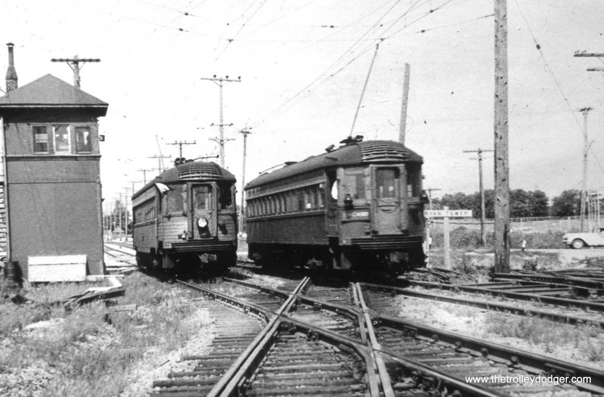 """Milwaukee County, WI - A pair of CNS&M cars (the """"Silverliner"""" at left is on a fantrip) pass one another at Ryan Tower - crossing with the C&NW """"New Line."""" Note that the once-double-tracked C&NW is now ut a single-track line through here (the one-time westbound main has been removed). The view looks north. (William Shapotkin Collection)"""