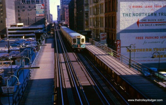 "In September 1964, at a time when the Loop ""L"" had uni-directional service (counter-clockwise), a Ravenswood ""A"" train approaches Clark and Lake. On the other hand, George Trapp says we are ""at Madison & Wells, notice the clocktower for Grand Central Station with B&O in distance. At that time many more cars is series 6001-6130 still had their original headlight arrangement."""