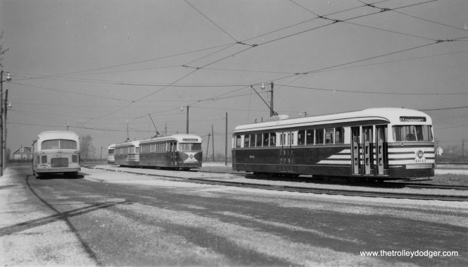 "CTA prewar PCC cars 4041, 4028, and others are on what appears to be the brand new turnaround loop at 63rd Place and Narragansett, which became the west end of Route 63 in 1948. The bus at left offered connecting service west of here. Previously, red streetcars ran to Oak Park Avenue, where they could easily turn back using a crossover, as they were double-ended. There is still a bus loop, although smaller, on this location. The first PCC is wearing ""tiger stripes,"" intended to improve motorist visibility, while its follower has the colors applied by CSL in 1941. (William Shapotkin Collection)"