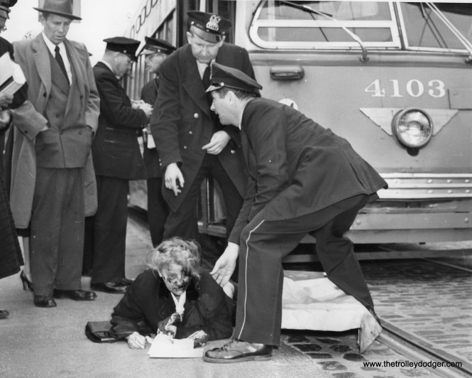 April 29, 1954: Anna Daltin, 69, of Chicago, shortly after being hit in the face by the edge of a Chicago streetcar, receives aid from police stretcher crew. she was taken to (the) hospital with a possible fractured nose and facial abrasions.