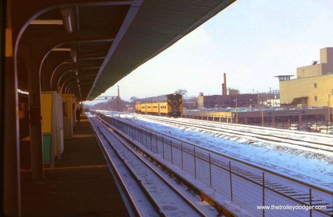 An eastbound Chicago & North Western commuter train is seen from the Harlem Avenue Station on the Lake Street 'L' on January 12, 1963, a few months after the CTA line was relocated onto the embankment. (J. W. Vigrass Photo)