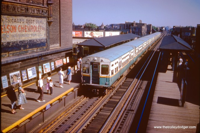 """A southbound Jackson Park """"B"""" train approaches the Belmont station on July 3, 1961. At left is the Vic Theater. Notice a Ravenswood train is also entering the station on the outer track."""