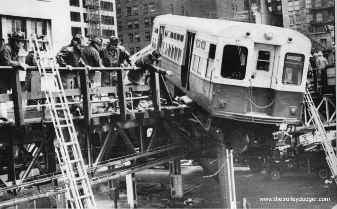 "As much as we would like Chicago ""L"" cars to remain on the structure, there have been a few times when they did not. This April 12, 1974 photo shows one that came pretty close to falling down, but fortunately did not. This looks like downtown, but I am not sure of the exact location. Andre Kristopans adds, ""Wreck was at Lake/Wells with 6047-48. Took W to N curve way too fast. This was probably last wreck cleaned up with only Rail derricks, S363 and S367. No rubber tired cranes used."""