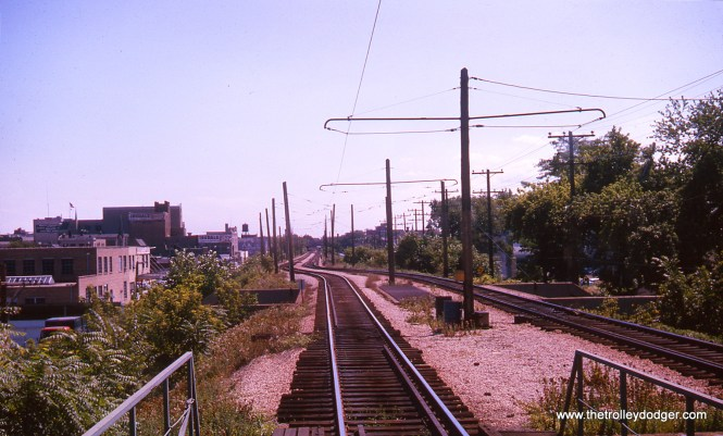 We are looking south off the rear of a northbound Evanston train at Foster Station in August 1963. The station in the distance is Davis Street.