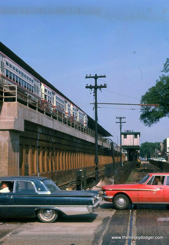 "Looking east from Harlem Avenue in 1963. The Lake ""L"" is now on the embankment, but the old tracks and the Marion Street station are still in place. A train of CTA's high-speed cars is in the station. The fans called them ""circus wagons."""