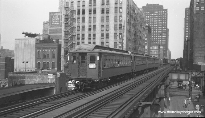 "A westbound Evanston Express train is on the Lake Street leg of the Loop near Clark.  The view looks east.  I assume this picture is from the 1940s, as the sign mentions Skokie instead of Niles Center.  Miles Beitler: ""There appears to be a propane bus in RBK275, visible just below the motorman's cab on the Evanston Train. If so, it dates the photo to 1950 or later.""  If so, why does the sign say Skokie, as the Niles Center route was converted to bus in 1948?"