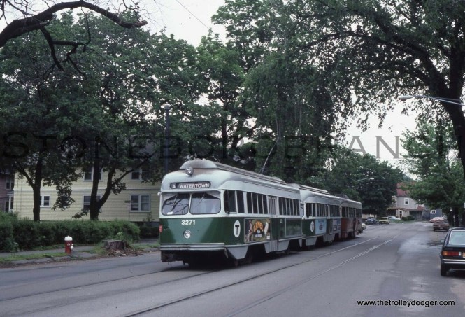 MBTA 3271 running as part of a multiple unit train on Tremont Street in Newton, MA on May 30, 1982. This may be a fantrip, as regular streetcar service on these tracks ended in 1969. Seeing a car signed for Route A - Watertown is quite rare, as the lettered routes were just being introduced around the time Watertown was bussed. The tracks and overhead remained in place for many years, for access to the Watertown car house, but have since been removed. The Watertown line fell victim to a car shortage in the late 1960s. It also had to cross an expressway and run against one-way traffic, another factor.