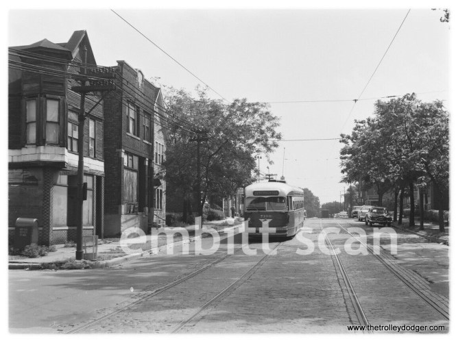 """CTA 7169 is southbound on Route 22 Clark-Wentworth. Perhaps this is somewhere on the south side, as I don't recall such a hill on the north side. Andre Kristopans: """"PCC on hill is a pullout heading east on 69th at Parnell."""" On the other hand, our resident south side expert M.E. writes, """"No scenes along Wentworth or Vincennes looked like this. So right away I thought this photo had to be along 81st St. Sure enough -- read the street sign at the left: 81st and Parnell."""" Robert Lalich: """"M.E. is correct on the location of CTA 7169. The street sign plainly shows 81st and Parnell. The WB car is about to duck under the C&WI tracks. Two of the three buildings on the left are still there."""""""