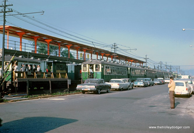 "2 of 2 Photos. Roger wrote on the slide mount, ""CTA eastbound Lake St. ""L"" taking down trolley pole at the station near N. Parkside Ave. and W. Lake St. in Chicago on August 14, 1962."" At street level the trains drew their power from the trolley wire overhead -- on the ""L"" structure from a third rail. This is the last station before this eastbound train mounts the ""L"" structure. Above the old station, up on the embankment, is the nearly completed new station. The elimination of trolley pole running on the western end of the Lake Street ""L"" allowed the CTA to modernize its fleet without the cost of trolley poles."