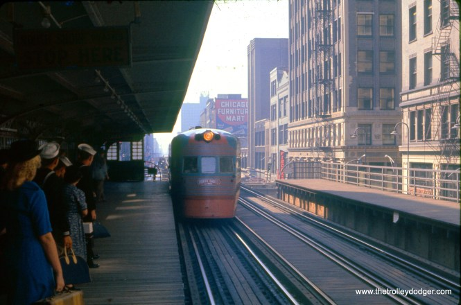 "A northbound Electroliner stops at Adams and Wabash on the Loop ""L"" in September 1959. While I am sure the sailors are about to board, chances are the woman in the blue dress is too, since she is carrying a small suitcase. (J. William Vigrass Photo)"