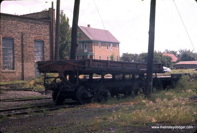 "J. William Vigrass took this picture in July 1960 and marked it as ""NSL"" at Harrison (presumably, by the shops in Milwaukee). Edward Skuchas: ""This is a Western 20 yard air dump car. They were used on railroads and trolley lines. Wilkes-Barre Railways had 2 or 3 and they adapted the ends for a radial drawbar. Car Works imported models in O & HO scale brass. They tilt and the sides lift."" David Cole thinks this may be the remains of the NSL weed sprayer shown in CERA B-106."