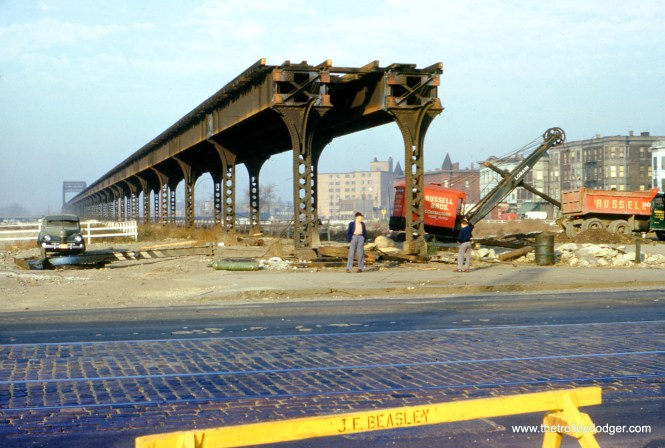 "On October 19, 1953, we are looking west along the old Garfield Park ""L"" at Western Avenue, as it was being demolished as part of the Congress expressway construction project. Behind the photographer, the Western Avenue ""L"" station was already being dismantled, which you can see in a different photo in this post. Remarkably, trains ran on these tracks as late as September 27 in one direction, only about three weeks before this picture was taken by William C. Hoffman. Soon, the Western Avenue streetcar tracks were re-routed in this area, so it could be excavated and the bridge that now goes over the expressway could be built."