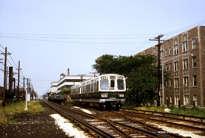 "This is the back end of a westbound two-car train of 2000s on the Douglas Park ""L"" in July 1966, approaching the Laramie Avenue station in Cicero. Laramie was closed in 1992, but was reopened in 2002-2003, while the nearby 54th Avenue station was being redone. The station house at Laramie has been declared historic and is the last remaining one of its type, and has been preserved, although no longer used."