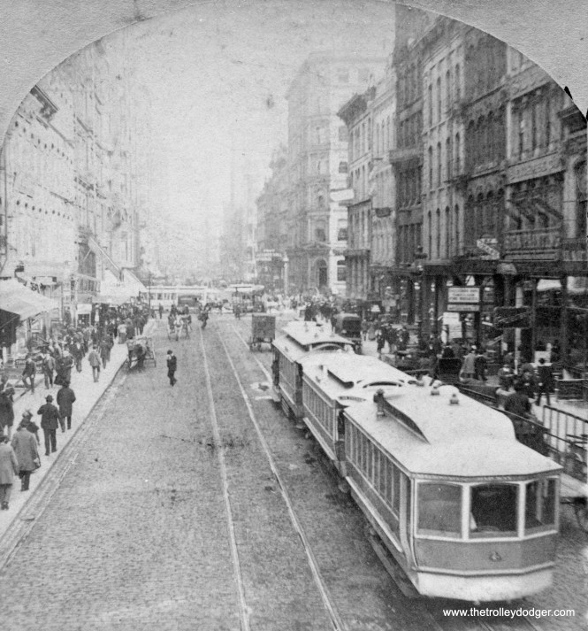 "Stereo images were popular around 1900, and when placed in the proper viewer (sometimes called a ""stereopticon"") provided a 3-D effect. This is the left picture from a stereo pair, showing cable cars on Madison Street in downtown Chicago. Some say that the Loop got its name from the paths taken by downtown cable cars, but research has shown the term came into popular use because of the ""L' and the Union Loop, completed in 1897. There are no overhead wires in view here, and none were permitted downtown until 1906. The tracks at left may have been used by horse car lines, since there is no trough for a cable."