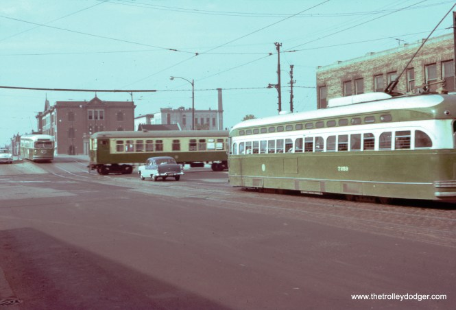 "On June 15, 1956, just two days before streetcars were replaced by buses on Western Avenue, two CTA PCCs meet a Garfield Park ""L"" train running on temporary trackage on Van Buren Street. (William C. Hoffman Photo)"
