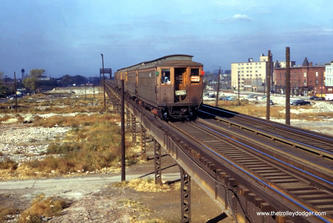 """On October 10, 1952, an eastbound five-car Garfield Park """"L"""" train approaches Western Avenue, where photographer William C. Hoffman was standing. The temporary trackage on Van Buren Street, visible at right, was then under construction."""