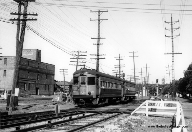 """CA&E 459 at the front of a two-car train. Could this be Wheaton? Dann Chamberlin: """"Again, yes it is. The photo looks like it could have been taken from the dispatcher's tower. That's the ever-present DuPage County courthouse tower in the background."""""""
