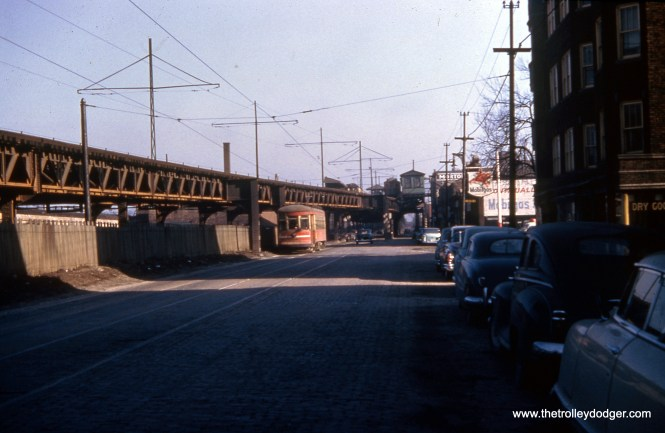 """We are looking east along Lake Street, just west of Laramie, in the early 1950s. The Lake Street """"L"""" descended to ground level here, running parallel to the CTA Route 16 streetcar for a few blocks. Streetcar service was replaced by buses on May 30, 1954."""