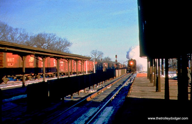 """February 22, 1956 at the Chicago & North Western's Lake Bluff station. At right, an eastbound passenger train arrives, while a westbound freight (coming off the """"New Line"""") passes. The view looks north."""