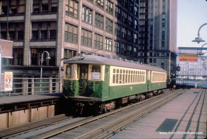 """A pair of 4000s are departing from the old Randolph and Wabash """"L"""" station on the Loop. The picture isn't older than 1959, as the Sun-Times/Daily News Building is in the background. It could be dated further, depending on whether those cars still have their trolley poles, which I think they do. Those were only needed until 1962. The 4000s were replaced by 2000s on Lake Street starting in 1964. Until 1969, the Loop was unidirectional, running counterclockwise, so these cars are heading away from us."""