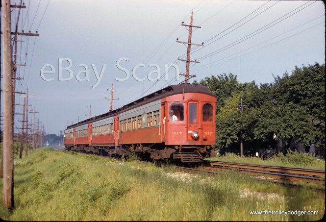 I am not sure just where this picture was taken, showing a westbound four-car train of CA&E woods, headed up by 317. The C&NW is at left. Guesses have so far included Glen Ellyn, Lombard, and Wheaton.