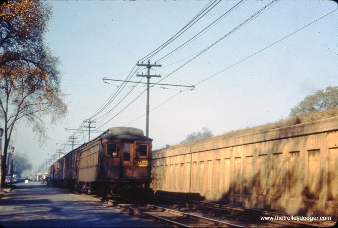 """An eastbound train of wooden """"L"""" cars (including 3210), with trolley poles up, heads east on the ground-level portion of the Lake Street """"L"""" in Oak Park on October 12, 1953. I believe the location is a few blocks east of Marion Street, where the street (South Boulevard) narrows."""