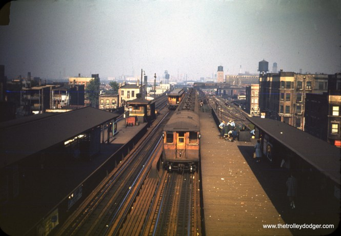 """Looking west from the passenger overpass at Indiana Avenue on July 3, 1950, we see an 8-car train of steel cars, and a Stock Yards shuttle train. In the distance, that may be some additional Stock Yards cars being stored on the otherwise unused center track. (William C. Hoffman Photo) Our resident South Side expert M. E. writes: """"Your caption needs correction. What you claim to be a Stock Yards shuttle is not on the Stock Yards tracks, which ran directly west from the switch building at the end of the platform. Instead, your """"Stock Yards"""" train is on the main line heading east/south. Apparently the CTA still ran old cars on the main line at that time, although I don't remember that. Another, more remote, possibility is that this short train is dead-heading east (without passengers) toward the Kenwood line. But in the next photo, you see no track connection from the main line to the Kenwood line. The only way dead-headed cars destined for Kenwood could end up on the Kenwood line would have been to turn south on the main line to 43rd St. and use switches to go from the southbound main line to the northbound main line to the former northbound main line track, which joined the Kenwood shuttle track back at Indiana Ave. -- and which (in reverse) provided the only way to move Kenwood cars off the Kenwood tracks."""" We were only repeating the information that Mr. Hoffman wrote on the original slide mount, which, of course, could be wrong."""