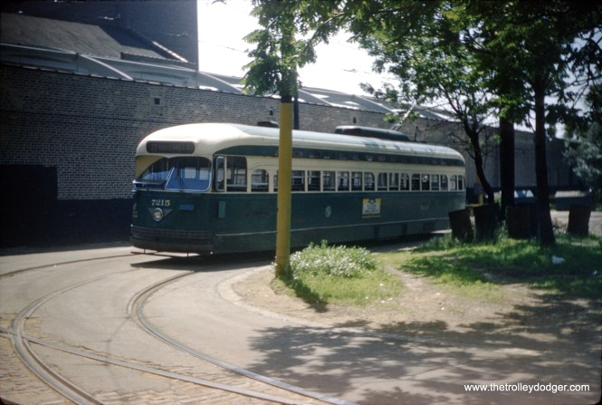 """CTA PCC 7215, a product of the St. Louis Car Company, is signed to go to 80th and Vincennes, operating on Route 22 - Wentworth in 1958. But was this picture taken at 80th and Vincennes? M. E. writes: """"Reason to think this photo was taken at 80th and Vincennes: There was a single loop track at 80th and Vincennes, and the terminal area was on the east side of a miniature """"park"""" situated east of Vincennes between the terminal trackage and Vincennes Ave. proper. Reasons to think this photo was not taken at 80th and Vincennes: (1) The exit trackage in the photo makes no sense if it were indeed 80th and Vincennes. The exit trackage ran straight out of the loop and onto northbound Vincennes trackage. (2) As I recall, 80th and Vincennes was a residential area with no large buildings. If I had to hazard a guess, I'd say this photo was taken on the property of the 77th/Vincennes carbarn, and the streetcar in the photo had either just returned from 80th and Vincennes or was headed there. This scenario is also likely because there was never a """"terminal"""" on line 22 at 77th St.; the closest was at 80th St. Consequently, streetcars in service coming from the north had to go to at least 80th St. before heading back to the barn at 77th St."""""""