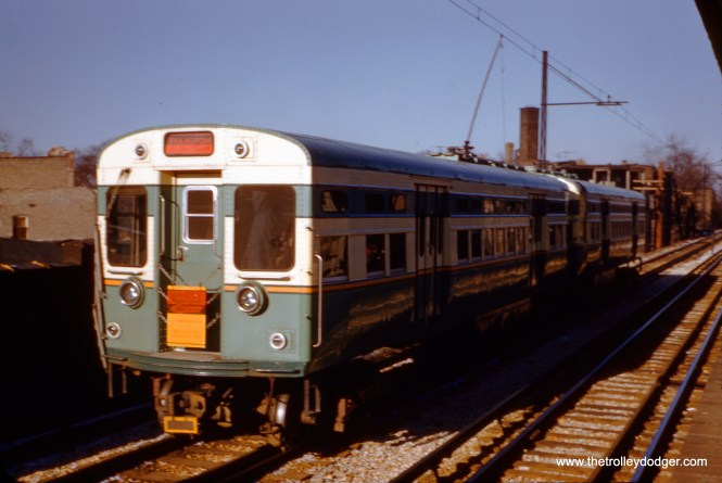 """CTA 6130-6129 are """"at speed"""" near Jarvis """"L"""" station on the north side, operating under wire on the southbound express track as a mid-day Evanston """"Shopper's Special"""" on December 11, 1955. The picture is slightly blurred because Kodachrome back then was ASA 10 (until the introduction of Kodachrome II in 1961). The unique signage on the train indicates which stations this express train stopped at."""