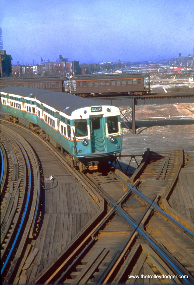 """A CTA train of 6000s is turning from the Metropolitan main line onto the Douglas Park """"L"""" on April 3, 1954, while a CTA test train (with car 2276) is on the new, as yet unused connecting track between the Douglas """"L"""" and the old Logan Square branch. Once Douglas trains began using this new """"L"""" connection, they began running downtown via the Lake Street """"L"""", and portions of the old """"L"""" east of here were torn down for expressway construction. By 1958, there was a new ramp in place, approximately in the same place the 6000s are here, leading down to the Congress rapid transit line in the expressway median. (Truman Hefner Photo)"""