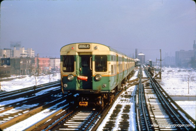 A train of CTA 6000s on the Metropolitan main line, looking east from Marshfield Avenue. This probably dates to late 1950, since no work has yet been done building the temporary right-of-way in Van Buren Street to the left, later used by Garfield Park trains. The tag on the train indicates whether it stopped at some part-time stations on Douglas. (Truman Hefner Photo)