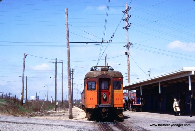 Chicago, South Shore and South Bend Railroad modernized interurban coach 28 and modernized steel interurban combine 107 at the end of the line station shared with Amtrak. The line was cut back from downtown South Bend in 1970. In 1992 the line would be diverted to the South Bend Airport. April 26, 1980, W Washington St & W Meade St, South Bend, Indiana. (Clark Frazier Photo)