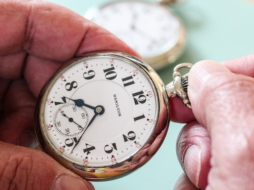 Winding the crown on a lever set pocket watch