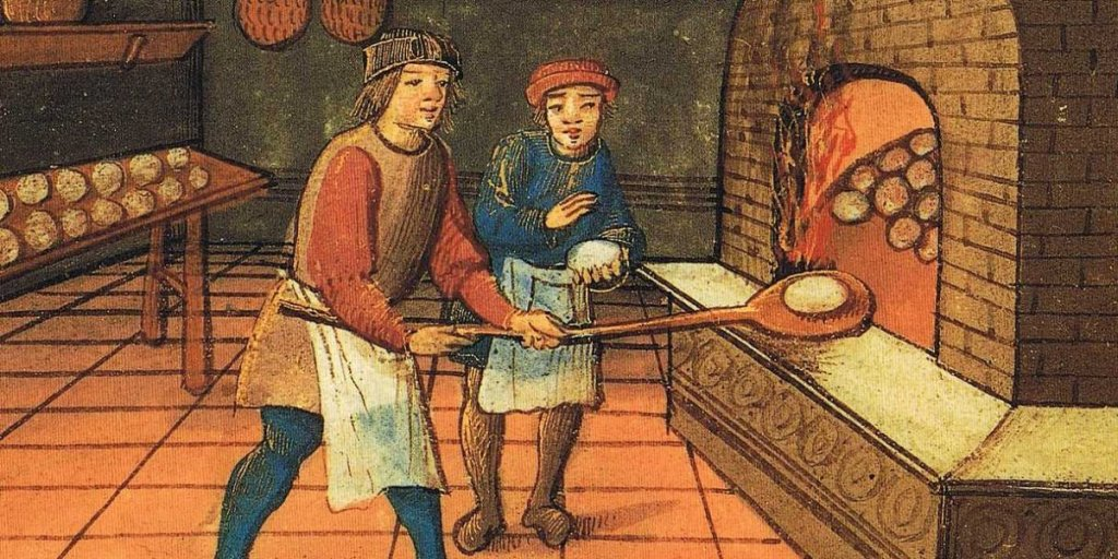 Two medieval bakers place bread in an oven to cook