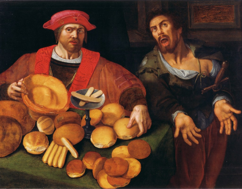 Two men sit before a table laden with different types of old-style bread.