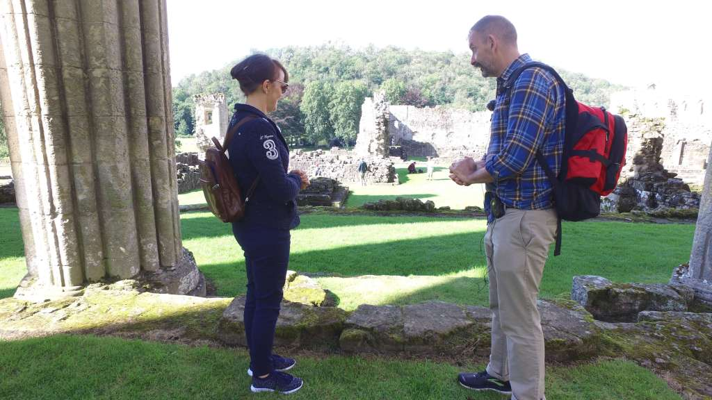 Two people in conversation looking at the ruins of a medieval sacristy