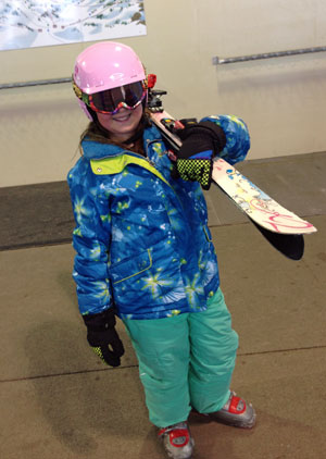 Carrying her own skis and smiling about it.