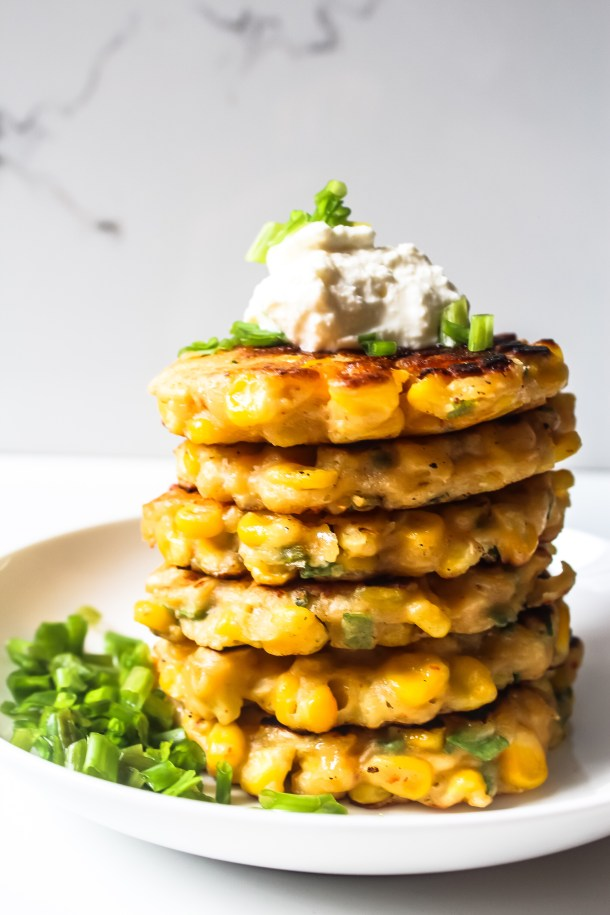 Corn fritters in a white plate topped with sour cream