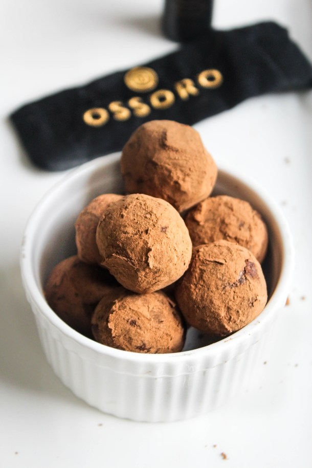 Brown chocolate truffles covered in cocoa powder placed in a white ramekin