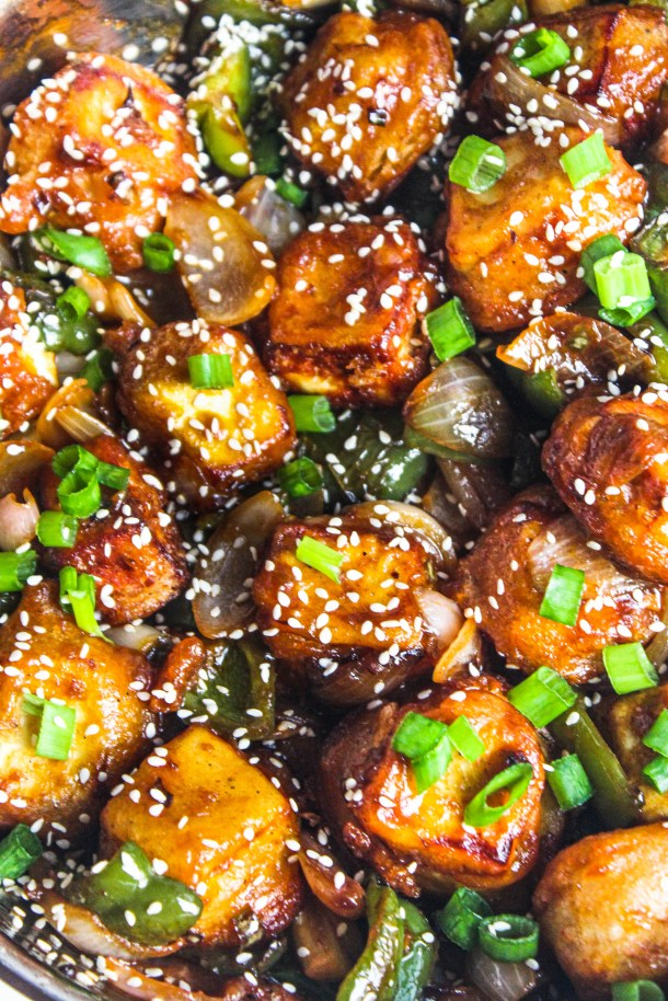 Red Brown Orange Paneer (Cottage Cheese) fried cubes tossed in a red chilli sweet and spicy sauce, topped with green spring onions and white sesame seeds.