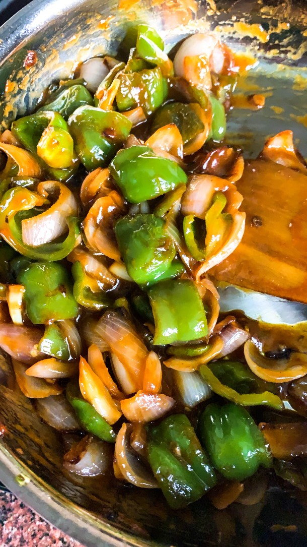 Green Capsicum and white pink onion tossed in a red sauce