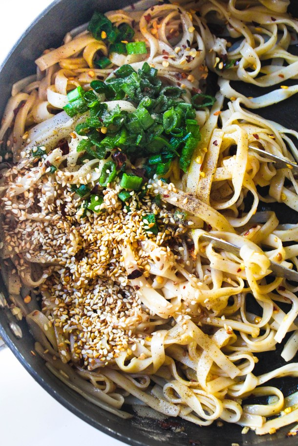 yellow flat rice noodles tossed in soy sauce, sesame oil and vinegar. Topped with green spring onions, toasted brown sesame seeds. Over a white bowl placed in a black pan