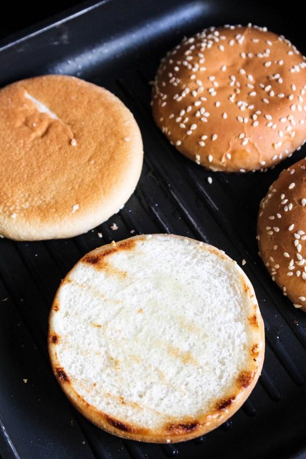 golden brown burger buns on a black griller