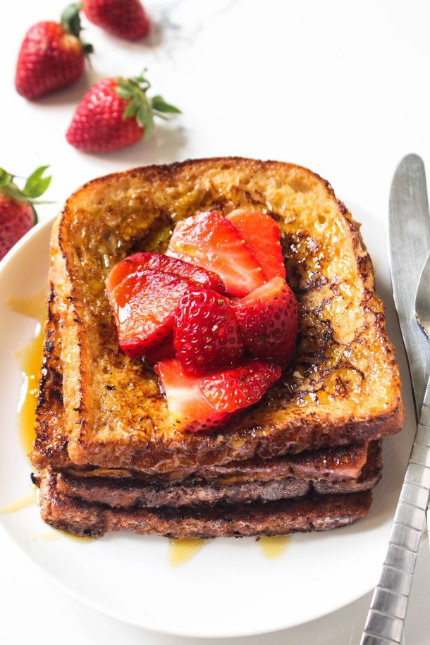 Brown cinnamon french toast stacks topped with red strawberries and honey drizzled on it. Served on a white plate placed on a white tile.