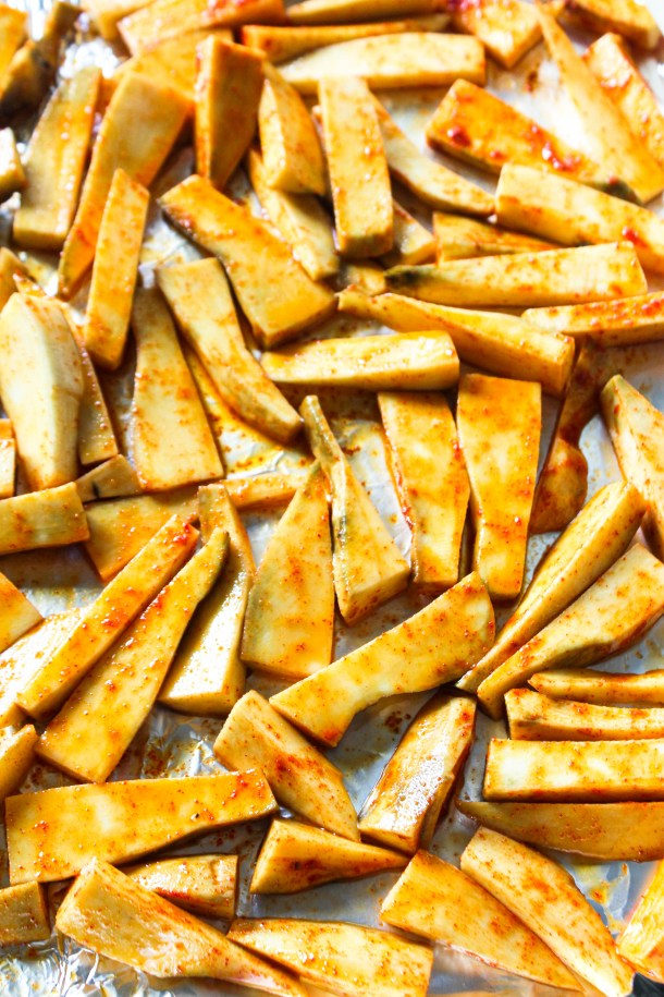 orange sweet potato chips of fries sprinkled with green spring onion and served with white mayonnaise on a black plate kept on a white tile.